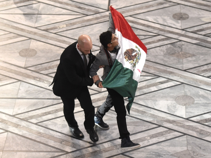 A security staff blocks a man holding a Mexican flag on the stage during the Nobel Peace Prize awarding ceremony at the City Hall in Oslo on December 10, 2014.  The 17-year-old Pakistani girls' education activist Malala Yousafzai known as Malala shares the 2014 peace prize with the Indian campaigner Kailash Satyarthi, 60, who has fought for 35 years to free thousands of children from virtual slave labour. AFP PHOTO / ODD ANDERSEN