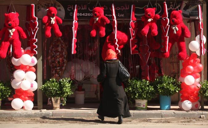 (150214) -- GAZA, febrero 14, 2015 (Xinhua) -- Una palestina se dirige a una tienda que exhibe osos de peluche y almohadas rojos en el Día de San Valentín, en la Ciudad de Gaza, el 14 de febrero de 2015. El Día de San Valentín es cada vez más popular entre los residentes de la región que han adquirido la costumbre de dar flores, tarjetas, chocolates y regalos a sus parejas para celebrar la ocasión. (Xinhua/Ashraf Amra/APA Images/ZUMAPRESS) (jg) (vf)